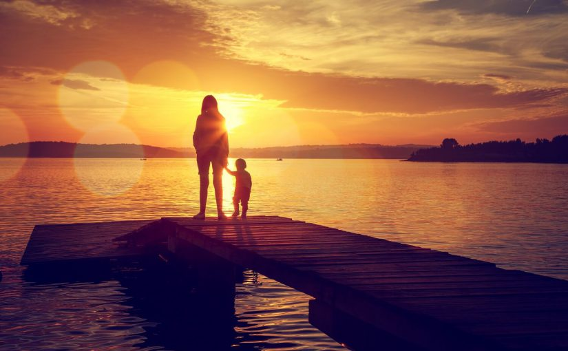 family standing on dock finger lakes in the summer