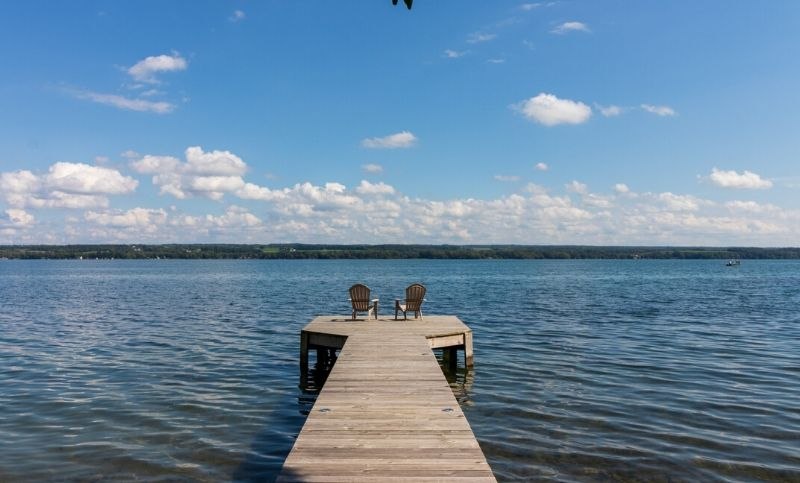 Dock on the lake with two chairs at the end