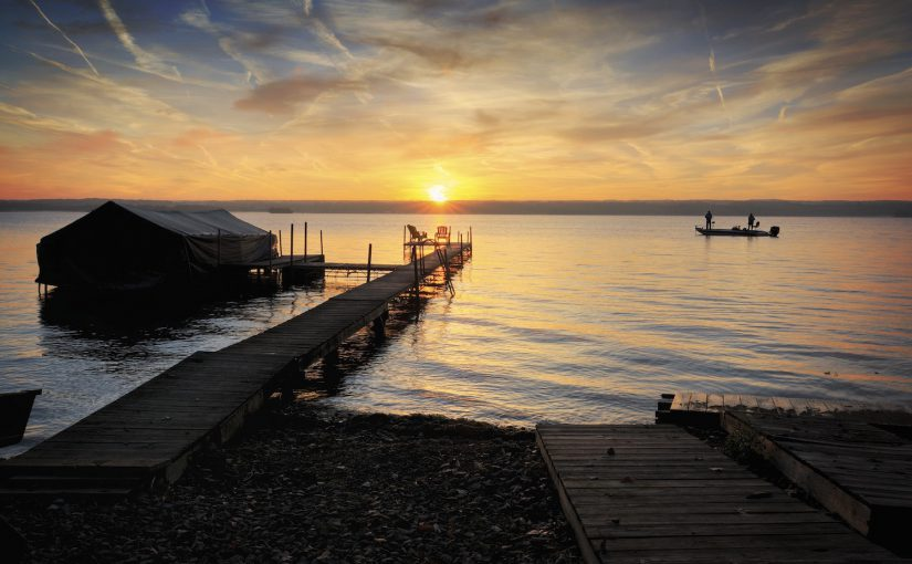 A beautiful autumn sunrise on the pebbled shores of Lake Cayuga in the Finger lakes region of New York state. A row boat with oars is docked on the side of a peir that leads out to a power boat shelter and a deck with chairs for watching the sunrise. Two fisherman enjoy the sunrise from their boat.