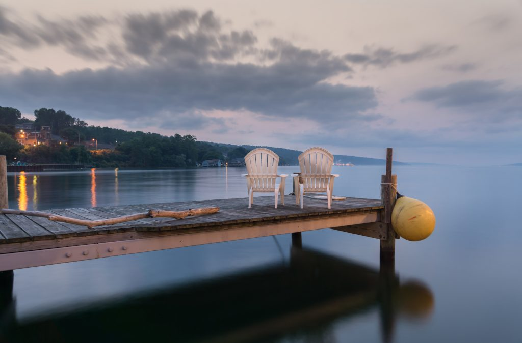 Two chairs sitting on a jetty at dusk, form a tranquil and idyllic scene at Lake Seneca, a popular vacation destination and located in the famous Finger Lakes region in New YorkState.